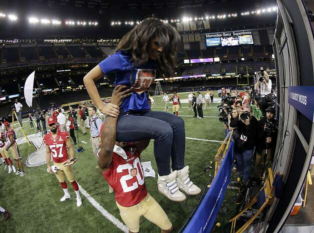 San Francisco 49ers defensive back Perrish Cox (20) lifts reporter Rosci Diaz during media day for the NFL Super Bowl XLVII football game Tuesday, Jan. 29, 2013, in New Orleans. (AP Photo/Charlie Riedel) Photo: Charlie Riedel, Associated Press