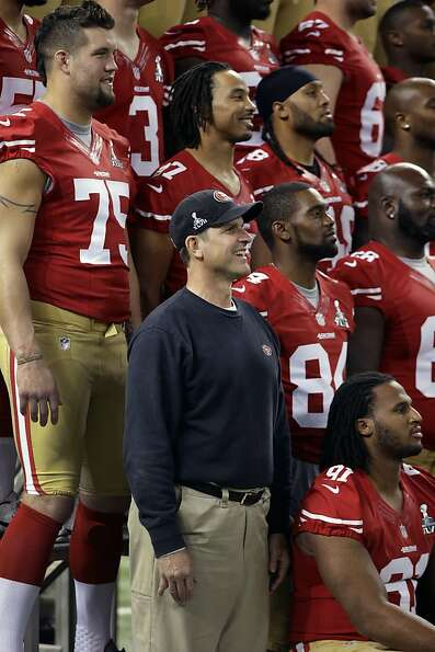San Francisco 49ers head coach Jim Harbaugh stands next to team of a photo during media day for the
