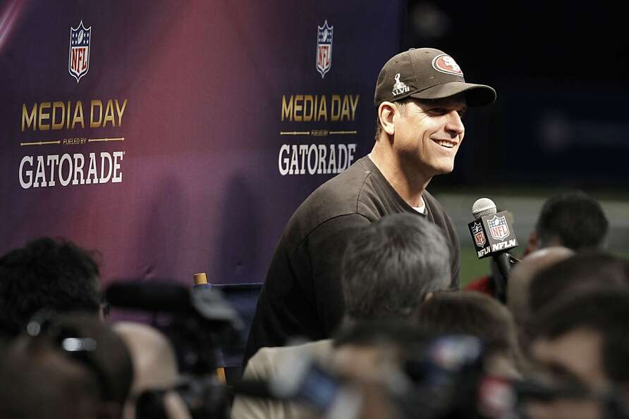 49er head coach Jim Harbaugh speaks to reporters as Media Day gets underway at the Mercedes-Benz Sup
