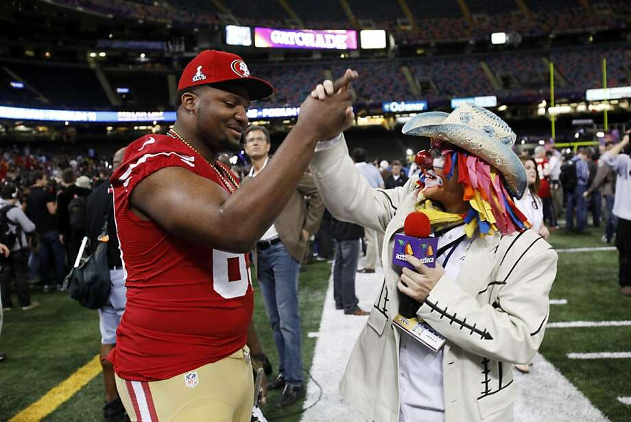 Tony Jerod-Eddie, left, high fives a TV Azteca reporter from Monterrey, Mexico who was dressed as a clown as the 49ers attended media day at the Super Dome in New Orleans, La., on Tuesday, January 29, 2013, as part of the Super Bowl festivities. Photo: Carlos Avila Gonzalez, The Chronicle