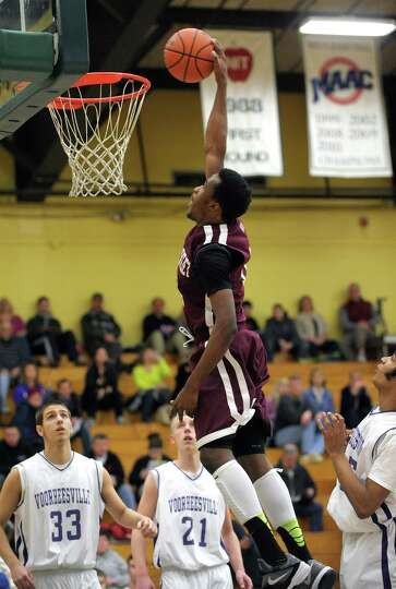 Tyler McLeod, right, of Watervliet goes up to dunk the ball during their game against Voorheesville