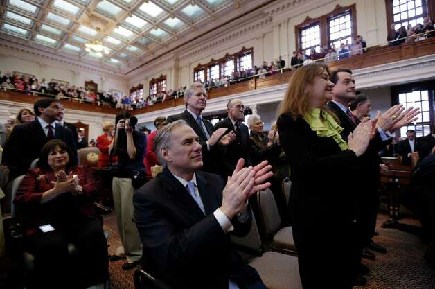 Texas attorney general Greg Abbott, center, applauds during Texas Gov. Rick Perry's state of the state address in the house chambers at the state capitol, Tuesday, Jan. 29, 2013, in Austin, Texas. (AP Photo/Eric Gay) Photo: Eric Gay, Associated Press / AP