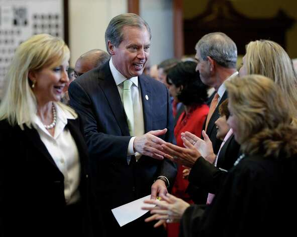 Texas Lt. Gov. David Dewhurst, center, and his wife, Tricia, left, arrive for Gov. Rick Perry's state of the state address in the house chambers at the state capitol, Tuesday, Jan. 29, 2013, in Austin, Texas. (AP Photo/Eric Gay) Photo: Eric Gay, Associated Press / AP