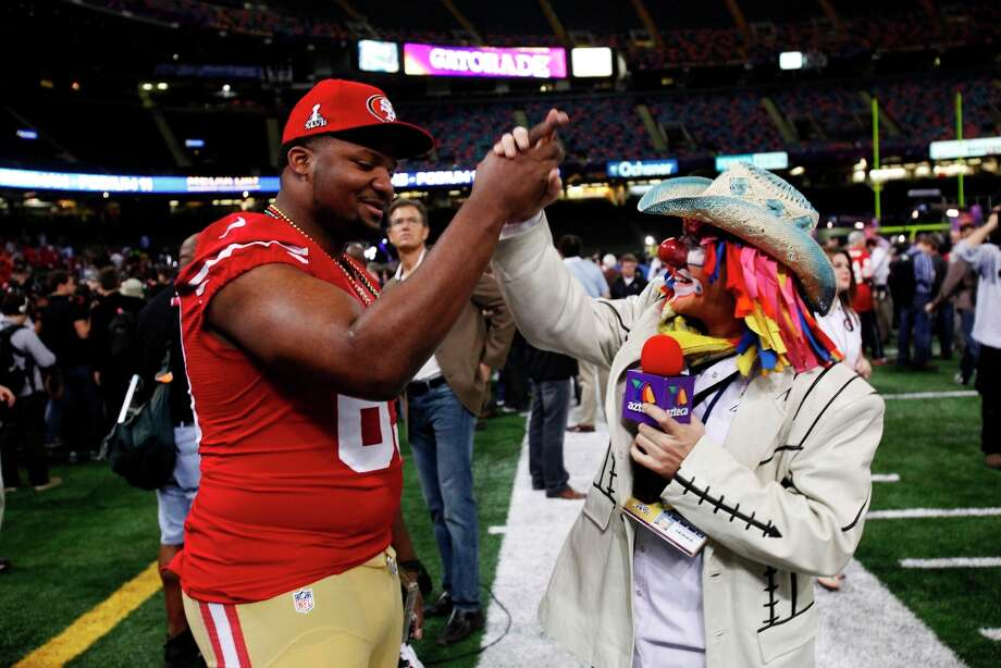 Tony Jerod-Eddie, left, high fives a TV Azteca reporter from Monterrey, Mexico who was dressed as a clown as the 49ers attended media day at the Super Dome in New Orleans, La., on Tuesday, January 29, 2013, as part of the Super Bowl festivities. Photo: Carlos Avila Gonzalez, The Chronicle / ONLINE_YES