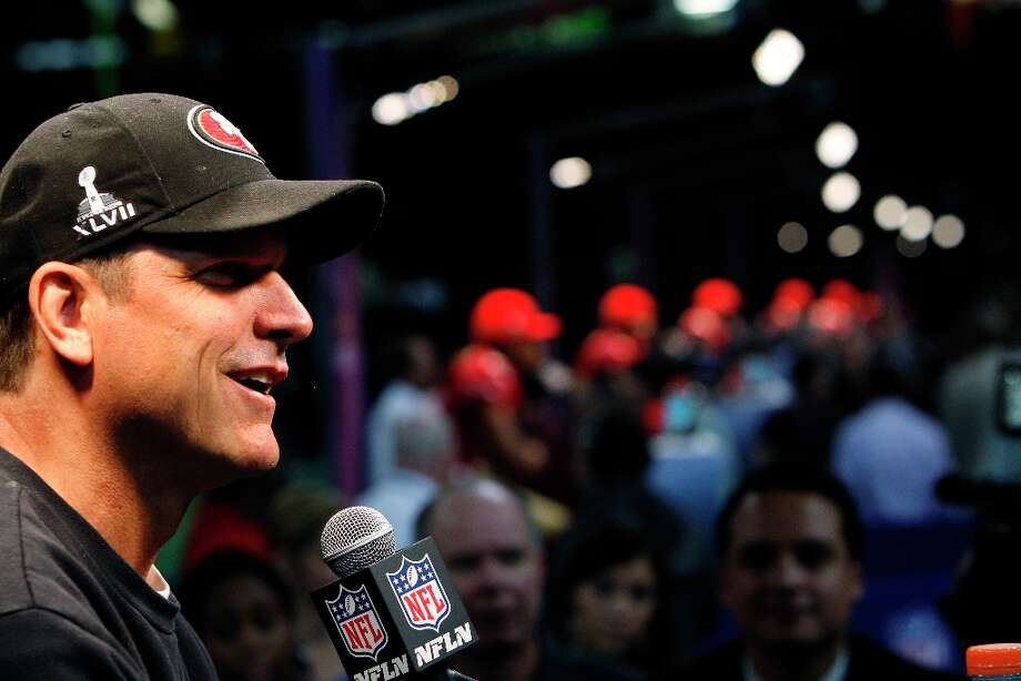 49ers coach Jim Harbaugh smiles as he answers a question from the press with his players behind him as the 49ers attended media day at the Super Dome in New Orleans, La., on Tuesday, January 29, 2013, as part of the Super Bowl festivities. Photo: Carlos Avila Gonzalez, The Chronicle / ONLINE_YES