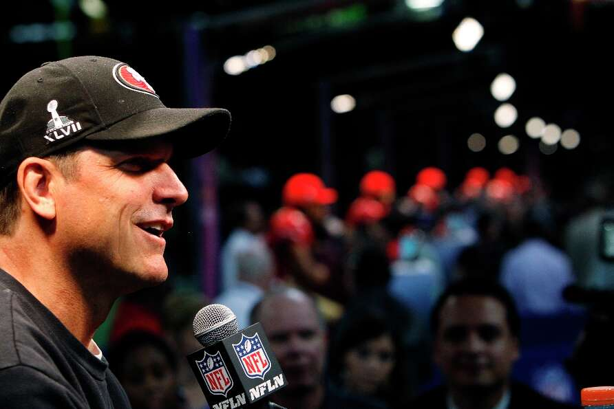 49ers coach Jim Harbaugh smiles as he answers a question from the press with his players behind him