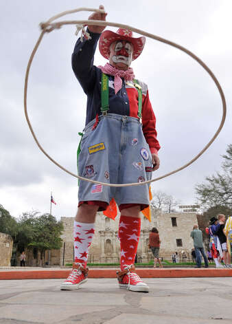 "Rodeo clown Larry ""Popi"" Nuckols uses his lasso during an Alamo Plaza announcement of the the 2013 Western Heritage Parade and Cattle Dr. which will be Saturday. Photo: Robin Jerstad"