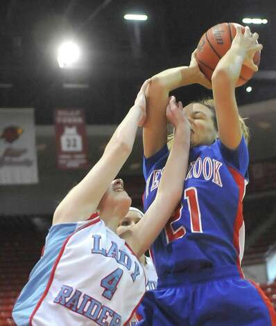 Lady Raider # 4, Hannah Holt, left, tries to block a shot by Lady Bruin, #21, Danielle Metoyer.  The Lumberton Lady Raiders and the West Brook Lady Bruins met on the court Thursday morning November 29, 2012 in a first round basketball game in the annual YMBL Basketball Tournament. The Bruins won 54-41.  Dave Ryan/The Enterprise Photo: Dave Ryan