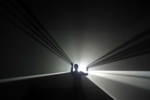 "Vanishing point: Anthony McCall's installation ""You and I, Horizontal"" casts long shadows at the Hayward Gallery in London. It's part of the Light Show exhibition, featuring 25 illuminated installations and sculptures from the 1960s to the present. Photo: Lefteris Pitarakis, Associated Press"