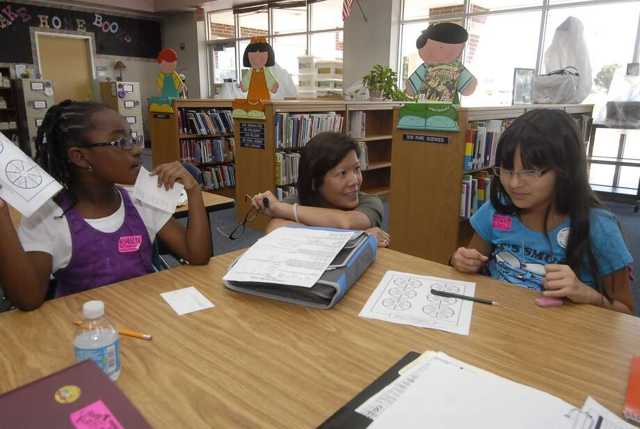 Edna McKenna, teacher and tutor, works with Ayana Williams, left, and Natalia Unigarro.  helping them with their 4th grade science homework during the after school Club Rewind program in the library at Birkes Elementary Tuesday 9/18/12. Photo:  Tony Bullard 2012, Freelance Photographer / © Tony Bullard & the Houston Chronicle