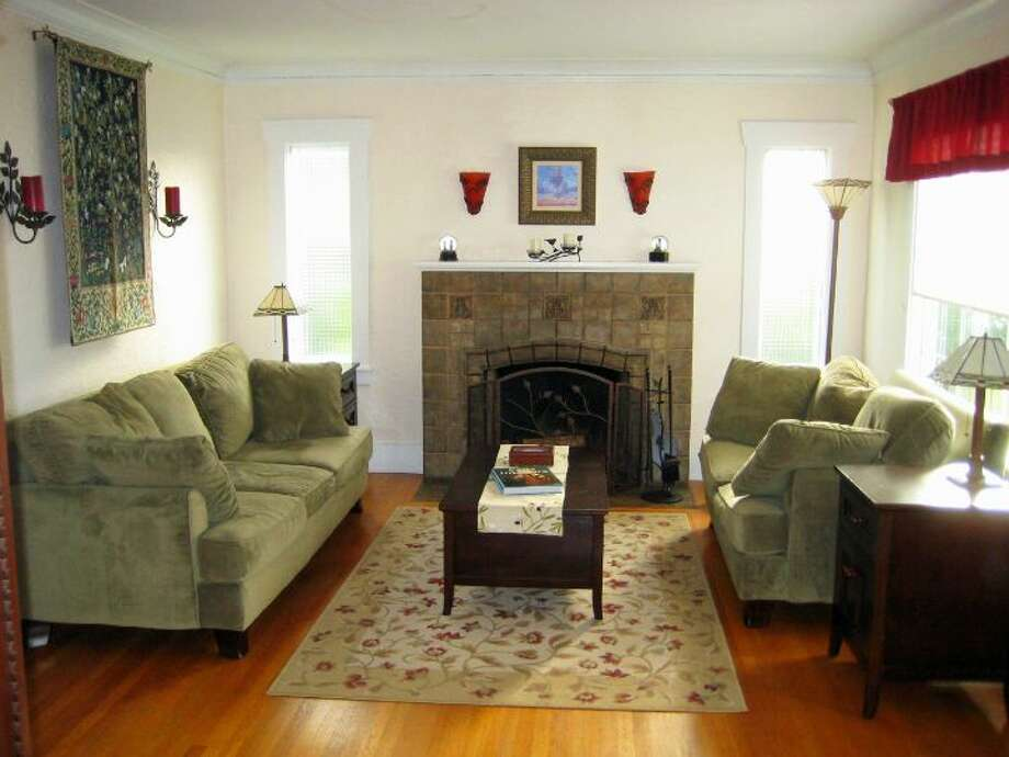 Living room of 6522 30th Ave. N.E. The 2,280-square-foot house, built in 1924, has three bedrooms, 1.75 bathrooms, arched doorways, coved crown moldings, a family room, a front porch and a back deck on a 4,500-square-foot lot. It's listed for $500,000. Photo: Courtesy Ken Shiovitz/Windermere Real Estate
