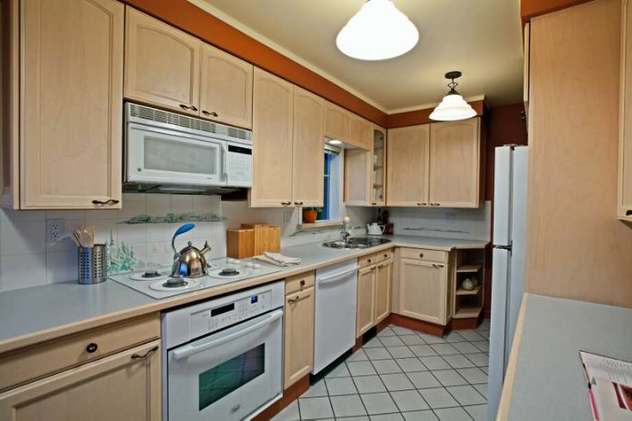 Kitchen of 7327 19th Ave. N.E. The 1,850-square-foot house, built in 1929, has two bedrooms, 1.75 bathrooms, a family room, coved ceilings, French doors, a front porch and a patio on a terraced, 3,060-square-foot view lot. It's listed for $499,900. Photo: Courtesy Bruce Johnson And Lisa Strain/Windermere Real Estate