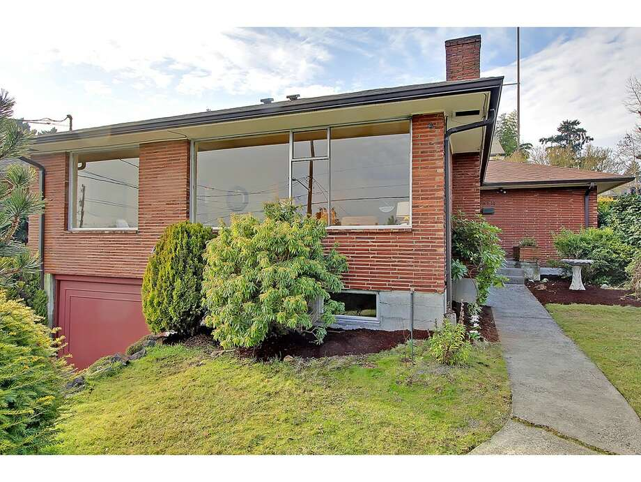 Shifting to mid-century brick, here's 6559 36th Ave. N.E. The 2,520-square-foot house, built in 1954, has three bedrooms, 1.75 bathrooms, big windows, a rec room with a fireplace and bar, and views of the Cascades on a 5,100-square-foot lot. It's listed for $525,000. Photo: Courtesy Carolyn Holm/Windermere Real Estate