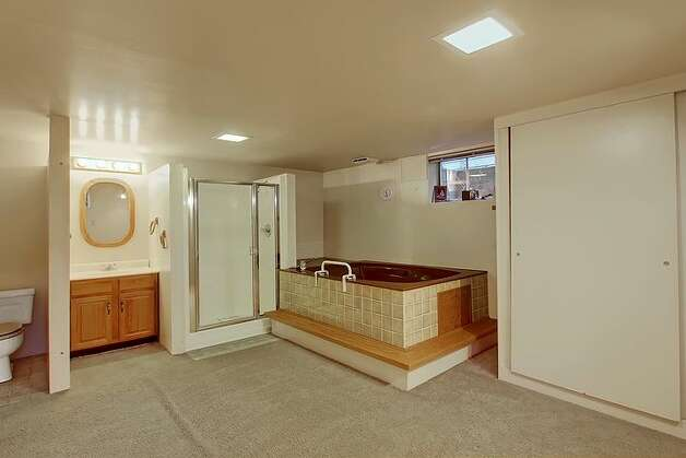 Bathroom of 6833 32nd Ave. N.E. The 2,540-square-foot house, built in 1950, has four bedrooms, two bathrooms, a rec room with a fireplace, a jetted tub and a backyard deck on a 4,000-square-foot lot. It's listed for $539,000. Photo: Courtesy Kelland And Eileen Lindsey/Windermere Real Estate