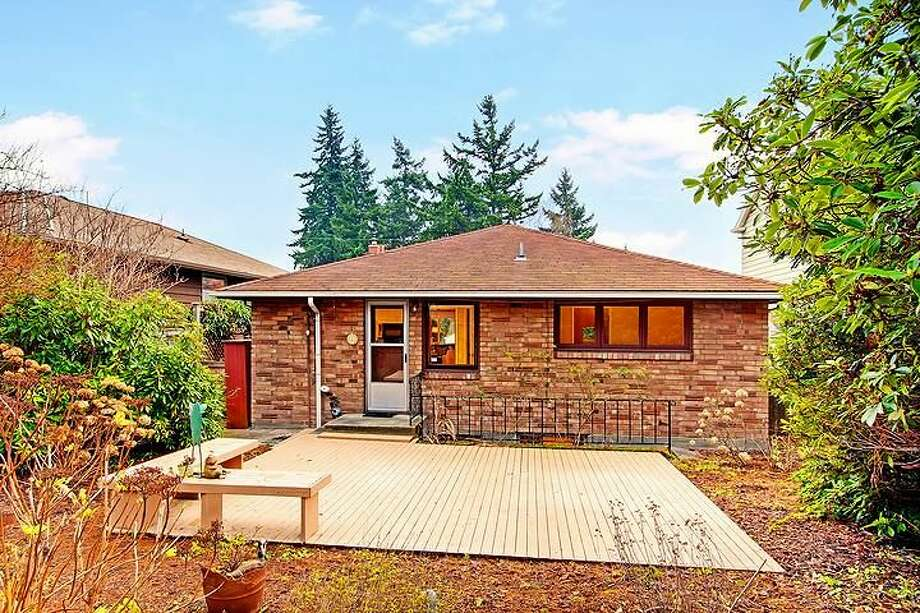 Backyard and deck of 6833 32nd Ave. N.E. The 2,540-square-foot house, built in 1950, has four bedrooms, two bathrooms, a rec room with a fireplace and a jetted tub on a 4,000-square-foot lot. It's listed for $539,000. Photo: Courtesy Kelland And Eileen Lindsey/Windermere Real Estate