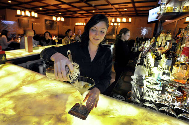 Heather Mandell, of Ridgefield, pours a vodka martini at the bar at The Cellar Door Bistro on 439 Main Street in Ridgefield, Conn., Friday, January 18, 2013. Photo: Carol Kaliff / The News-Times