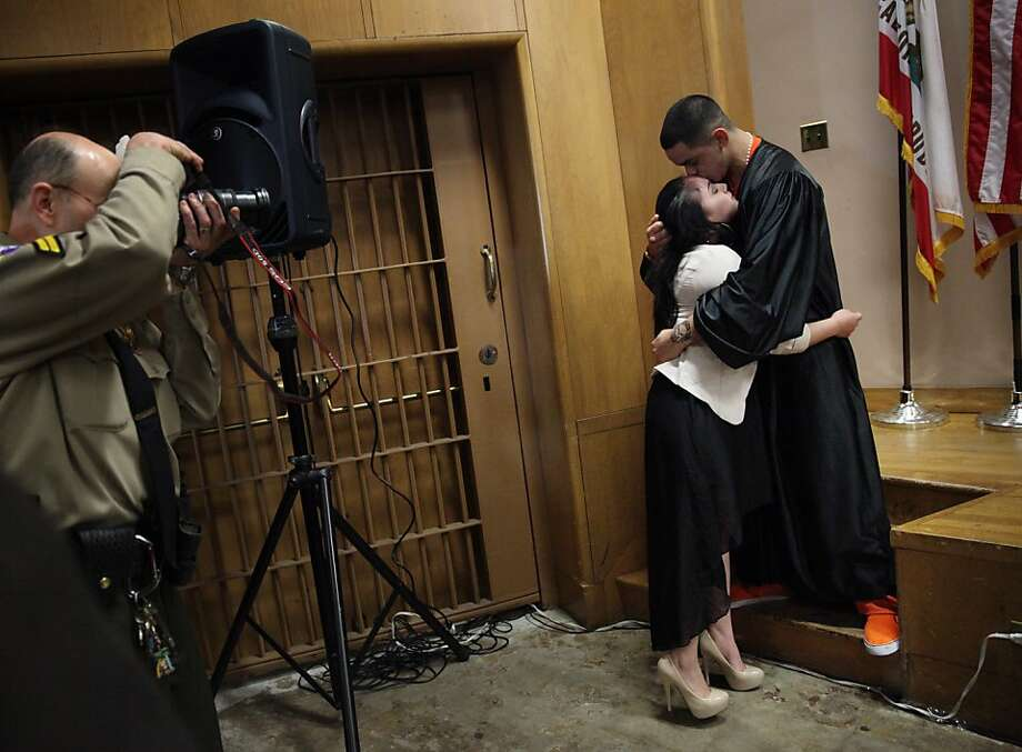 Mayte Lopez hugs Kristopher Viana after Viana receives his diploma at the Five Keys Charter School graduation. Photo: Lea Suzuki, The Chronicle