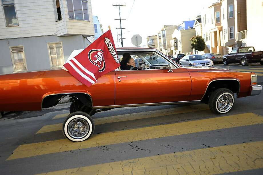 Jackie Marquez sits in the passenger seat of her 1983 Cadillac Coupe de Ville as it heads through the Mission, jacked up on its hydraulics, top. Photo: Michael Short, Special To The Chronicle