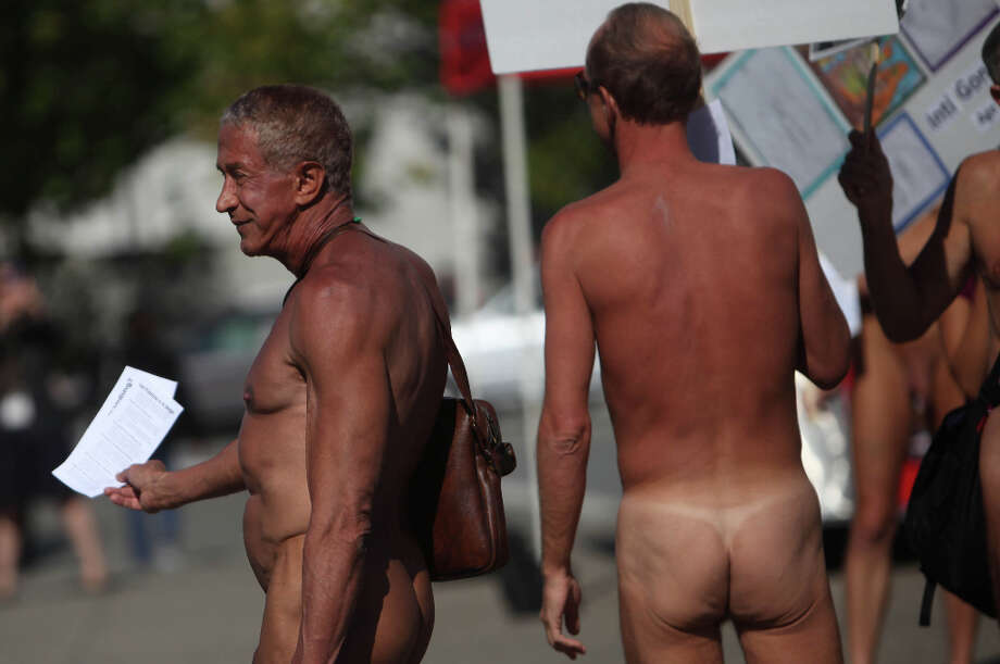 Rusty Mills (left) of San Francisco, hands out leaflets across from City Hall as he and other demonstrators gather to  protest Supervisor Scott Weiner's proposal to ban nudity in the city except at certain functions on Tuesday, October 30, 2012 in San Francisco, Calif. Photo: Lea Suzuki, The Chronicle / ONLINE_YES
