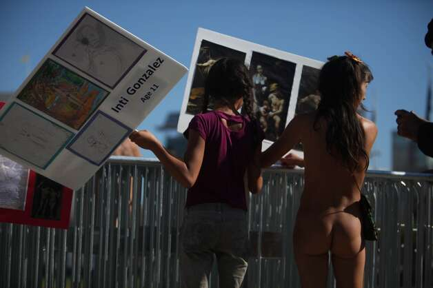 Gypsy Taub (right) organizes signs as her daughter Inti Gonzalez (left), 11, carries one she and her brother made as they gather with other demonstrators gather to  protest Supervisor Scott Weiner's proposal to restrict public  nudity in the city on Tuesday, October 30, 2012 in San Francisco, Calif.