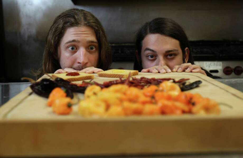"""Jeremiah Tallerine, left, and James Nelson, co-owners of Bravado Spice, marvel at the possibilities these chili peppers can bring to their products. """"Our sauces have such unique flavors,"""" Nelson says. Photo: Karen Warren, Staff / © 2012  Houston Chronicle"""