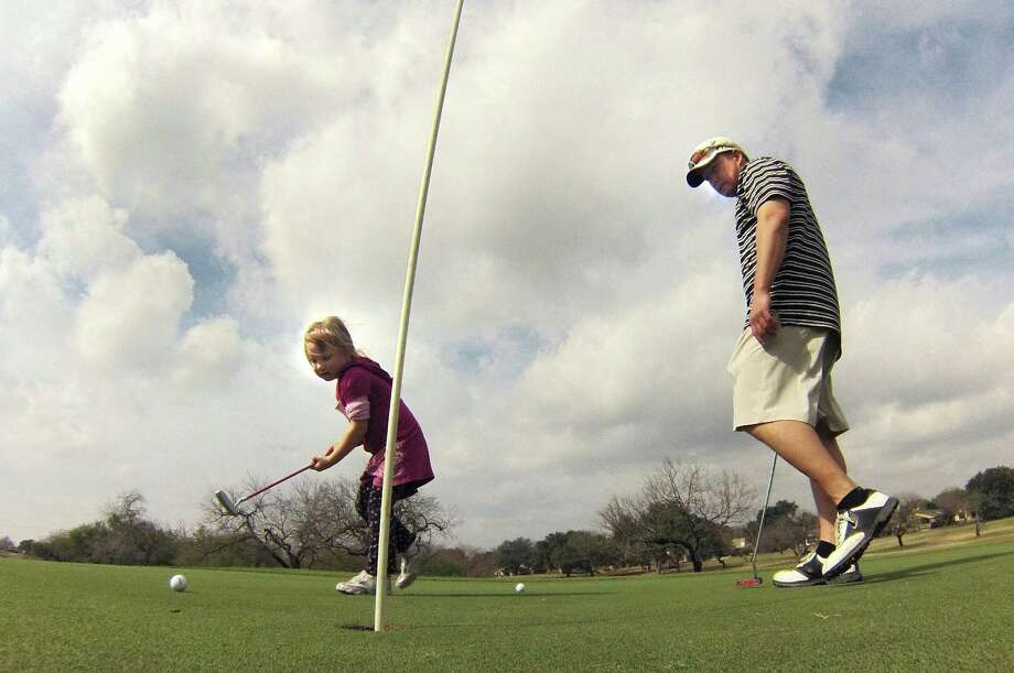 Chris Marcinowski and his daughter Lily play a round at Northern Hills Golf Club on the North Side. Northern Hills was one of many area tracts that enjoyed a modest hike in rounds played last year. Photo: Billy Calzada, San Antonio Express-News / © 2012 San Antonio Express-News