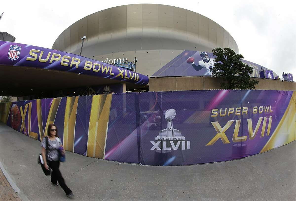 A pedestrian walks past the Superdome where the San Francisco 49ers and the Baltimore Ravens will play the NFL Super Bowl XLVII football game, Tuesday, Jan. 29, 2013, in New Orleans. (AP Photo/Charlie Riedel)
