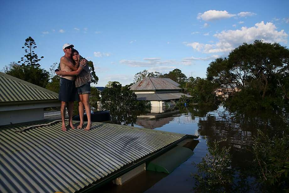 A man and his daughter assess the damage to their neighborhood from their roof in Bundaberg, southern Queensland. Photo: Chris Hyde, Getty Images