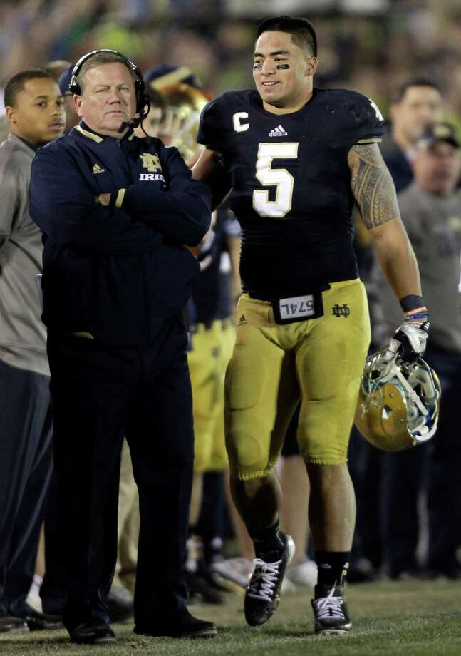 FILE - In this Nov. 17, 2012, file photo, Notre Dame linebacker Manti Te'o, right, pats coach Brian Kelly on the back after Te'o left the game during the second half of an NCAA college football game in South Bend, Ind. Kelly, talking to the media for the first time since the BCS title game, is expected to talk about his interview with the Philadelphia Eagles and the Te'o situation during a teleconference Tuesday. (AP Photo/Michael Conroy, File) Photo: Michael Conroy