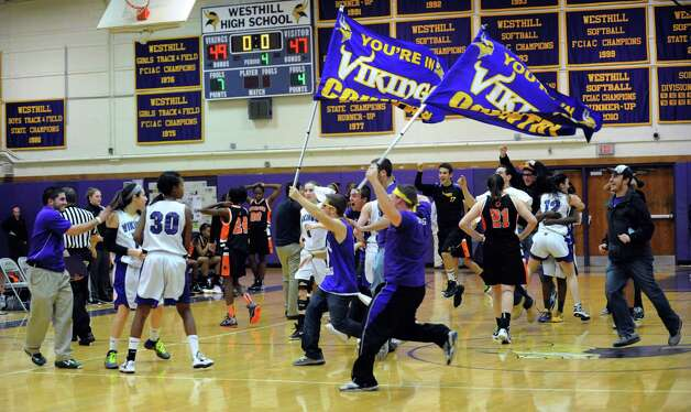Westhill fans rush the court after their team beat Stamford in Tuesday's girls basketball game at Westhill High School on January 29, 2013. Photo: Lindsay Perry / Stamford Advocate