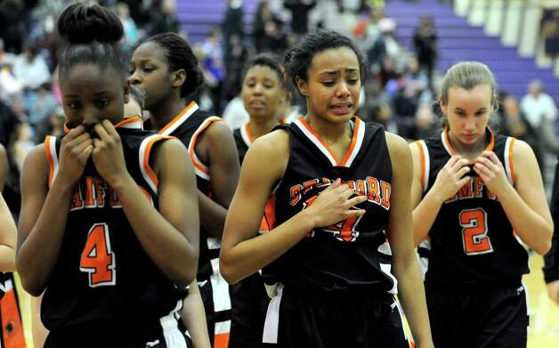 Stamford players including, from left, Camry Evans, Brianna Gordon and Alex Lemekha react after losing Tuesday's girls basketball game at Westhill High School on January 29, 2013. Photo: Lindsay Perry / Stamford Advocate