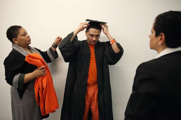 Juan Alay (center) gets assistance from CheRonn Piper (left), site coordinator, County Jail 5, and Terese Bravo (right), assistant director of education, as he dons his graduation gown and cap outside a holding cell at the San Francisco County Jail #3 to prepare for the San Francisco Sheriff Department's Five Keys Charter School graduation ceremony in the Hall of Justice 6th floor auditorium on Tuesday, January 29, 2013 in San Francisco, Calif.