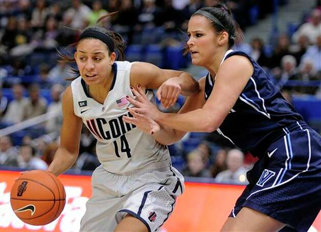 UConn's Bria Hartley, left, drives past Villanova's Jesse Carey during the first half of an NCAA college basketball game in Hartford, Conn., Tuesday, Jan. 29, 2013. (AP Photo/Fred Beckham)