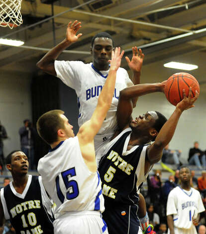 Bunnell players #1 Ryan Pittman, top, #15 Timothy White block Notre Dame of Fairfield's #5 Earl Coleman as he tries to make a shot, during boys basketball action in Stratford, Conn. on Tuesday January 29, 2013. Photo: Christian Abraham / Connecticut Post