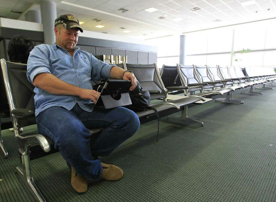 Waiting for his flight on British Airways to Kenya at Bush Intercontinental's Terminal D, Billy Randles works on his iPad. The Sealy resident gave a big thumbs up when informed of the airport system's WiFi plans. Photo: Karen Warren, Staff / © 2013 Houston Chronicle