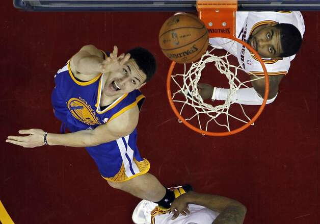 Golden State Warriors' Klay Thompson, left, flips in a shot against Cleveland Cavaliers' Kyrie Irving in the fourth quarter of an NBA basketball game Tuesday, Jan. 29, 2013, in Cleveland. Thompson led the Warriors with 32 points in a 108-95 win. (AP Photo/Mark Duncan) Photo: Mark Duncan, Associated Press
