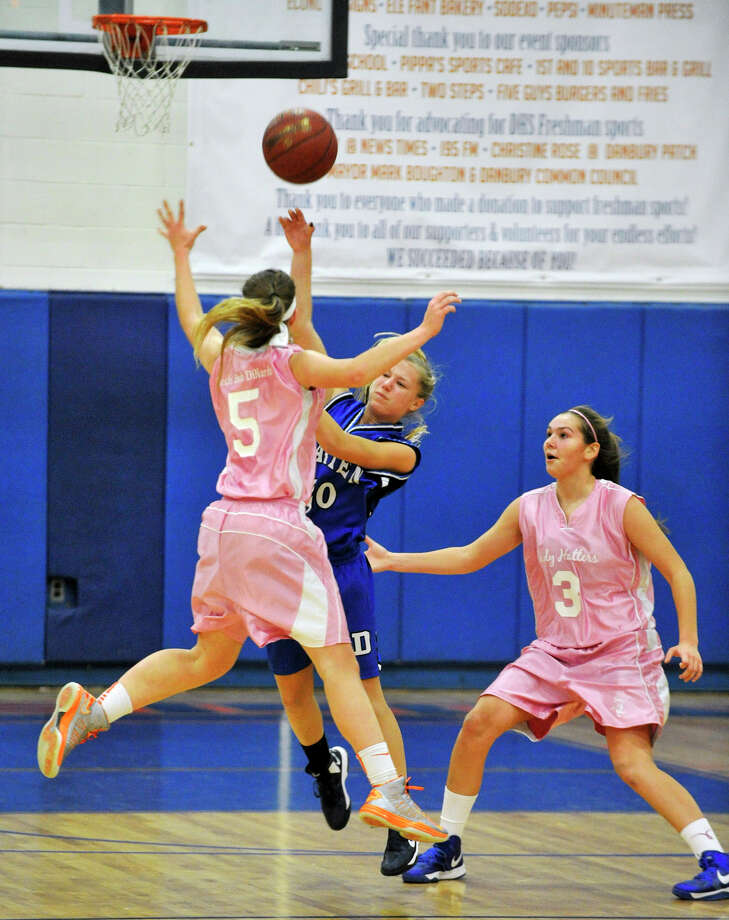 Darien's Kelly Karczewski finds an open teammate over the jumping Rachel Gartner, of Danbury, during their game at Danbury High School on Tuesday, Jan. 29, 2013. Danbury won, 51-44. Photo: Jason Rearick / The News-Times