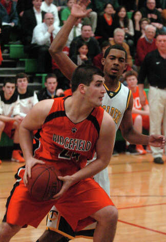 Ridgefield's Andrew Barton moves the ball as Trinty's Neno Merritt blocks as Trinity Catholic hosts Ridgefield High School in a boys basketball game in Stamford, Conn., Jan. 29, 2013. Photo: Keelin Daly / Keelin Daly