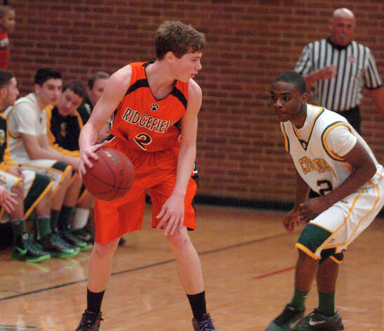Ridgefield's Charlie Irwin moves the ball as Trinity's Schadrac Casimir defends as Trinity Catholic hosts Ridgefield High School in a boys basketball game in Stamford, Conn., Jan. 29, 2013. Photo: Keelin Daly / Keelin Daly