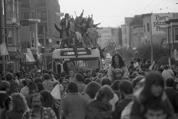 Fans celebrating the 49ers Super Bowl XVI win celebrate by climbing on top of a Muni bus on Union Street. Jan. 24, 1982.