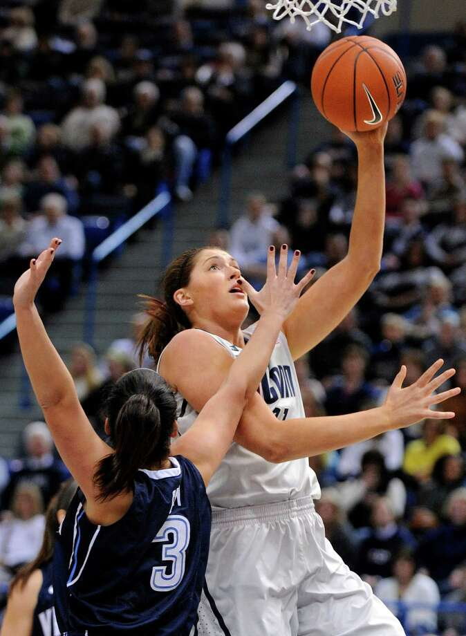 Connecticut's Stefanie Dolson, right, scores while being guarded by Villanova's Jesse Carey during the first half of an NCAA college basketball game in Hartford, Conn., Tuesday, Jan. 29, 2013. (AP Photo/Fred Beckham) Photo: Fred Beckham, Associated Press / FR153656 AP