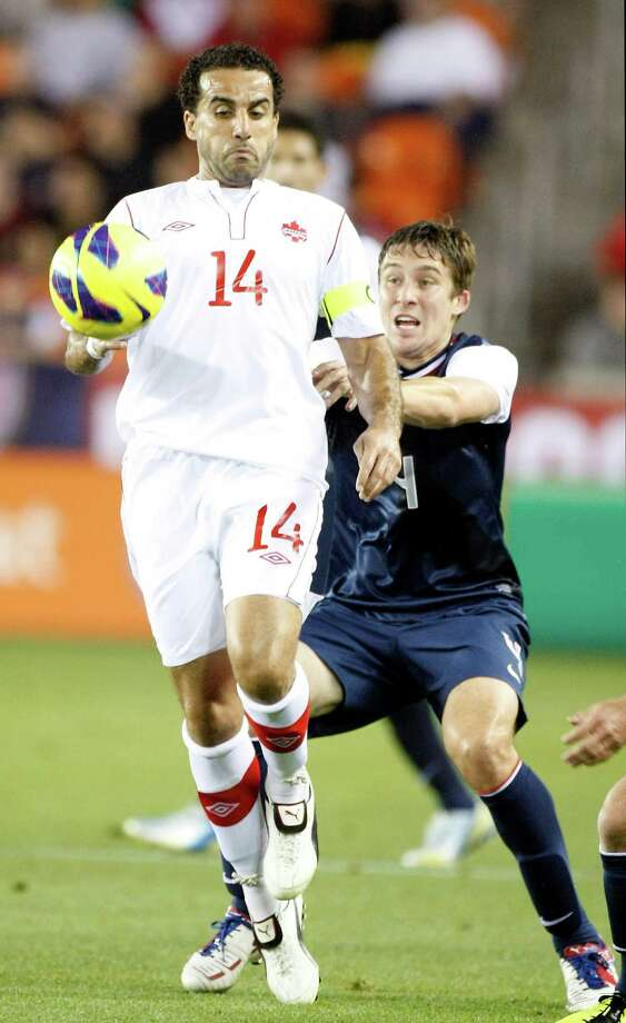 Canada's Dwayne De Rosario looks to maintain control of the ball as USA's Matt Besler adds pressure during the first half. Photo: Nick De La Torre, Houston Chronicle / © 2013  Houston Chronicle