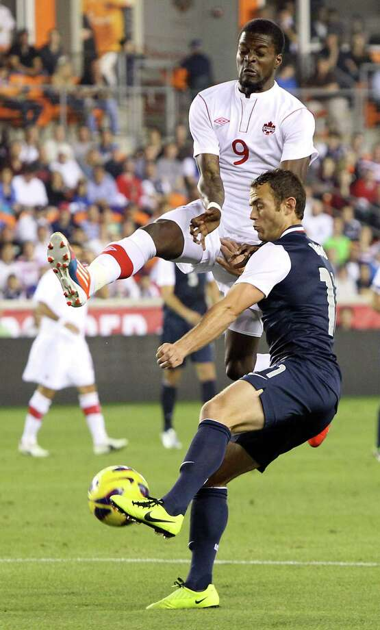 Canada's Tosaint Ricketts, top, prevents USA's Brad Davis from centering the ball during the first half. Photo: Nick De La Torre, Houston Chronicle / © 2013  Houston Chronicle