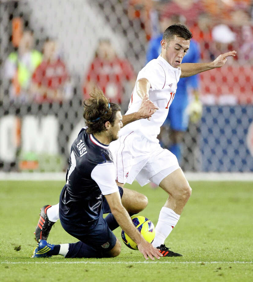 USA's Graham Zusi is pushed down by Canada's Russell Teibert during the first half. Photo: Nick De La Torre, Houston Chronicle / © 2013  Houston Chronicle