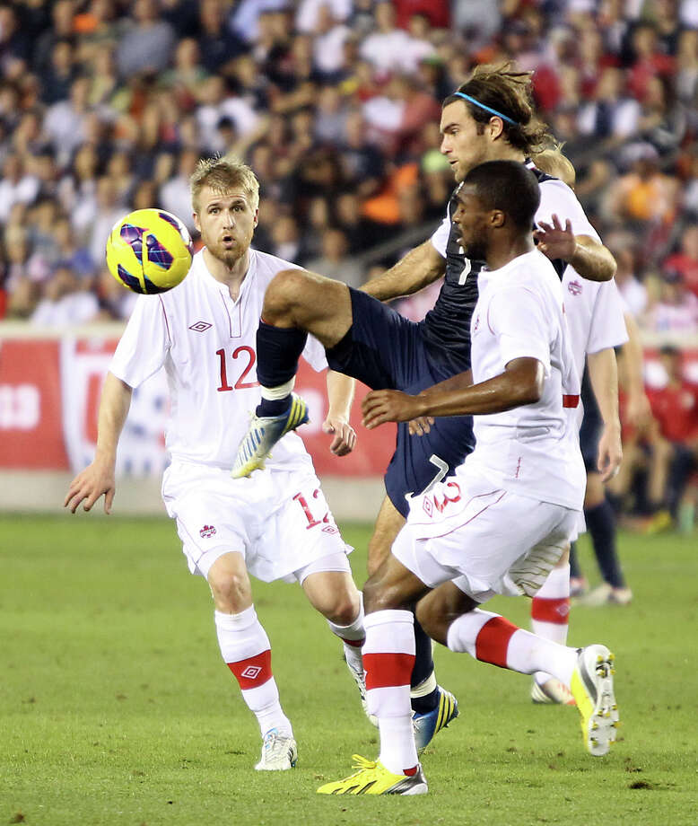 USA's Graham Zusi is prevented from taking a shot on goal by Canada's Ashtone Morgan during the first half. Photo: Nick De La Torre, Houston Chronicle / © 2013  Houston Chronicle