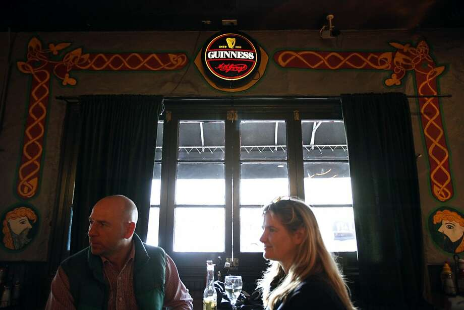 Ian Dunne, Susan Houlihan drink at Phoenix Bar on Valencia Street, which got off easy when vandals hit the Mission after the World Series. Photo: Sarah Rice, Special To The Chronicle