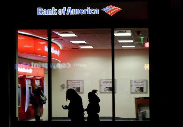 In this Thursday, Dec. 13, 2012 photo people use a Bank of America ATM in Boston. Banks including JPMorgan Chase, U.S. Bancorp and Bank of America seized on government payments for unemployment compensation as a business opportunity and pitched card programs to many states. However to cover the costs of the programs, banks have hit all card users with a plethora of new fees. Photo: Charles Krupa, Associated Press / Associated Press