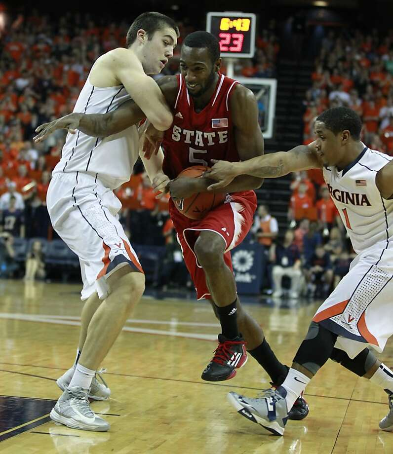 N.C. State's C.J. Leslie drives between Mike Tobey (left) and Jontel Evans, but the No. 19 Wolfpack lost to Virginia. Photo: Ethan Hyman, McClatchy-Tribune News Service