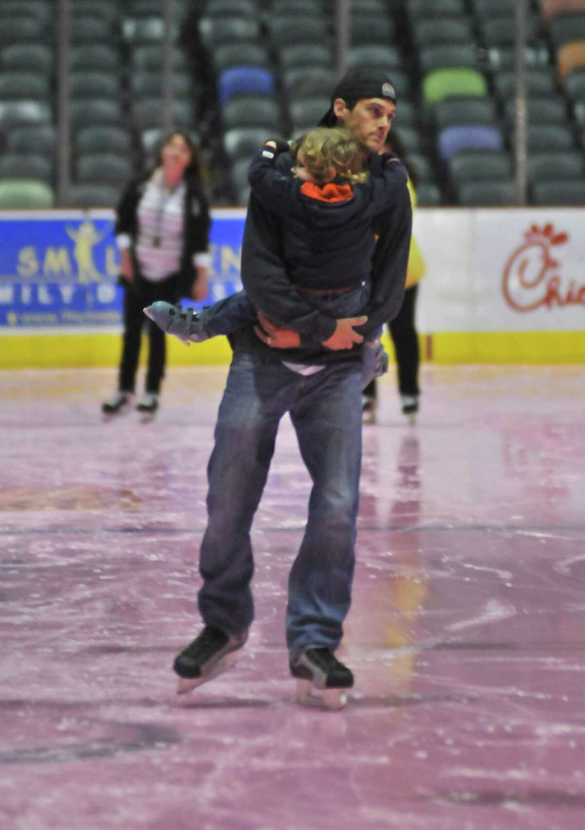 Paul DeYoung carries his 2-year-old son Liam while skating on the pink ice during the San Antonio Rampage Pink in the Rink Skate on Jan. 29. The ice at the AT&T Center is pink to commemorate breast cancer awareness.