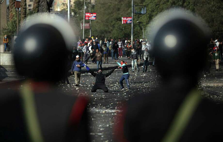 Egyptian protesters clash with riot police near Tahrir Square, Cairo, Egypt, Tuesday, Jan. 29, 2013. Intense fighting for days around central Tahrir Square engulfed two landmark hotels and forced the U.S. Embassy to suspend public services on Tuesday. (AP Photo/Khalil Hamra) Photo: Khalil Hamra